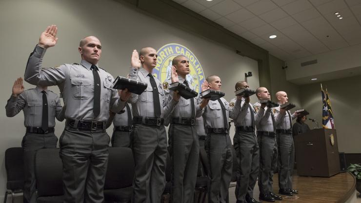 state troopers at attention with hands on Bible