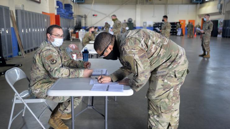 NC National Guard soldier registering at a table with others in background