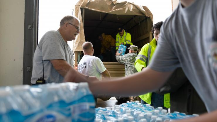 five men loading cases of bottled water into a national guard truck