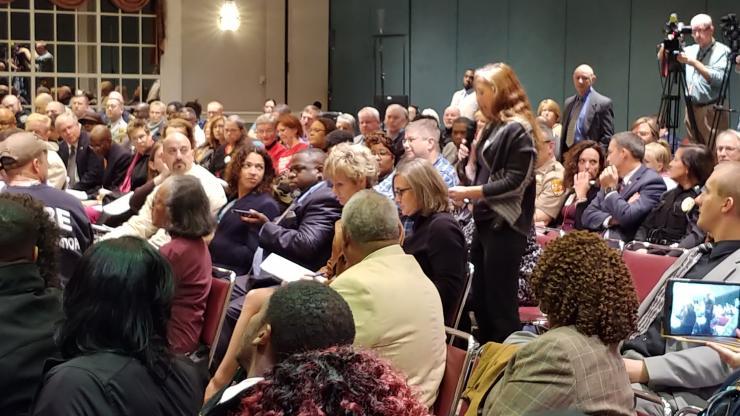 Group of people in meeting in large room