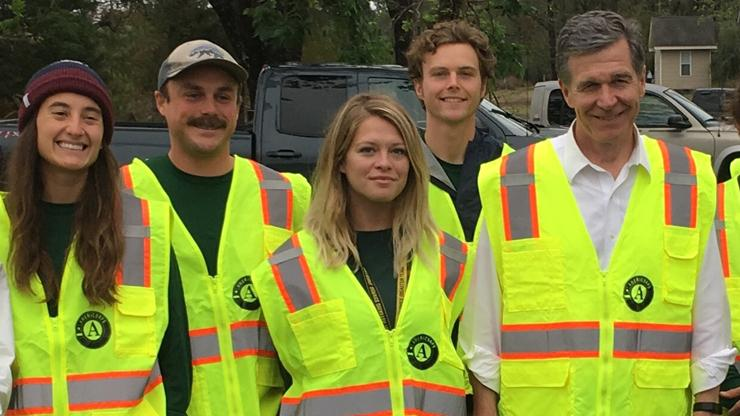 Americorps members with Governor Roy Cooper all wearing yellow vests