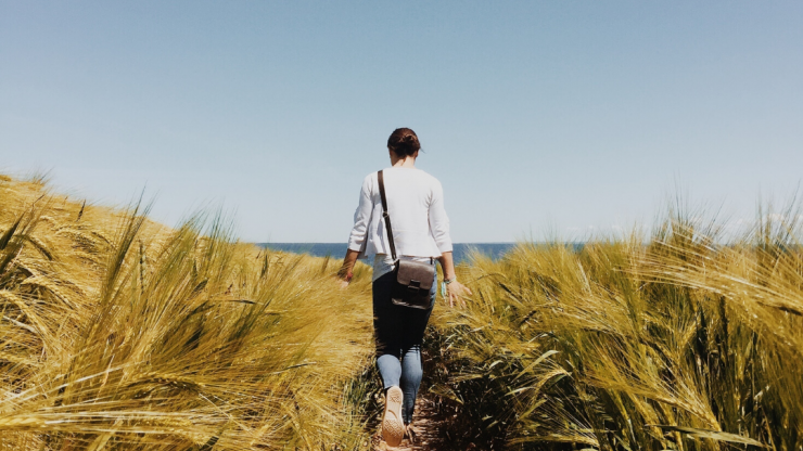 Woman walking on a path between tall grass