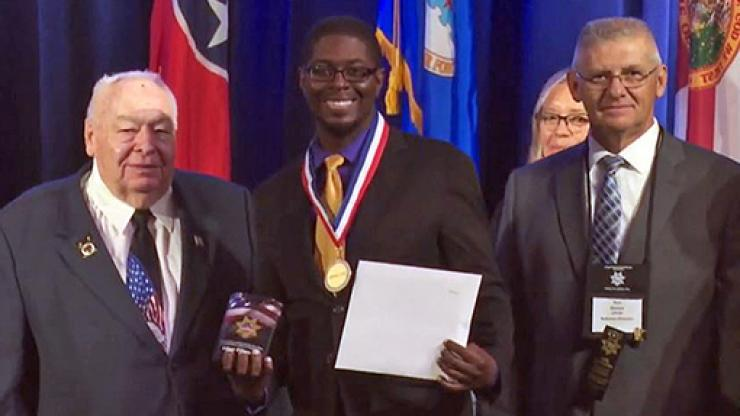 man in center wearing medal and holding certificate with man on either side