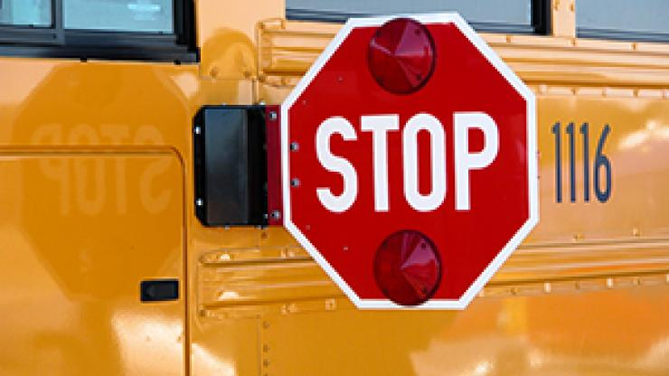 side of school bus with stop sign extended