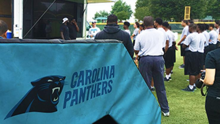 Carolina Panthers table in foreground; people standing in background