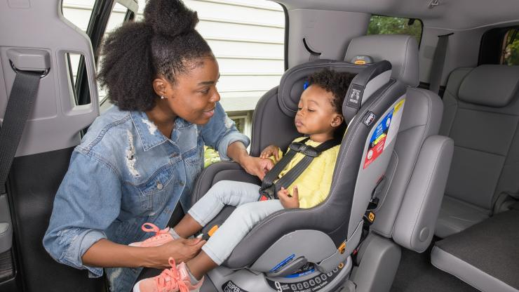 Woman strapping in child to a forward-facing car seat