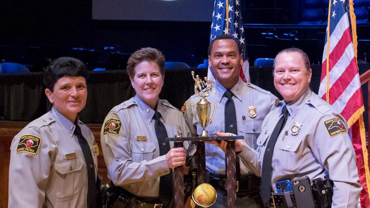 Lt. Col. Carter holding trophy with Col. Glenn McNeill and standing with two other female SHP members