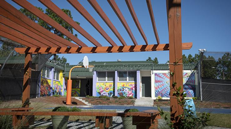 pergola in foreground with brightly colored painted walls of building in background