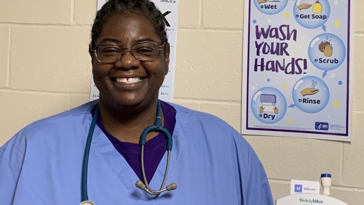 nurse in scrubs smiling for camera