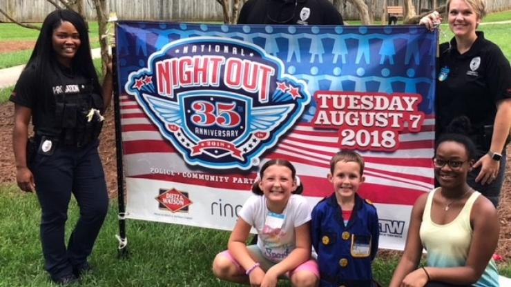 3 officers and 3 children standing near National Night Out banner