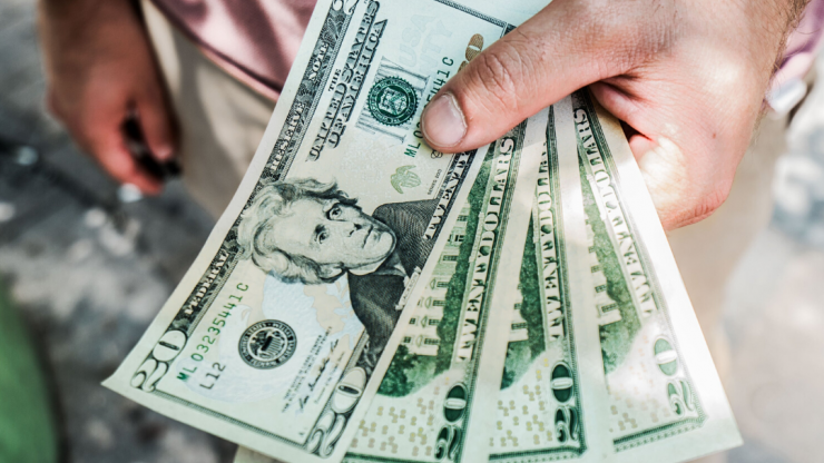 Man holding four $20 bills