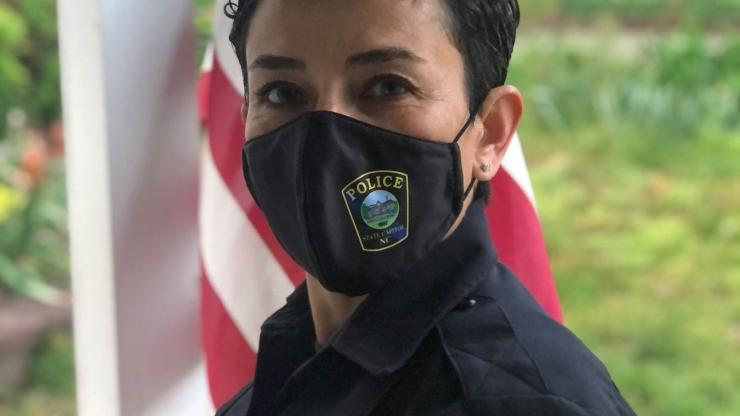 """Woman with short, black hair in black uniform that has a patch on arm that reads """"Police State Capitol, NC"""". Her mask has a smaller version of the patch on it."""