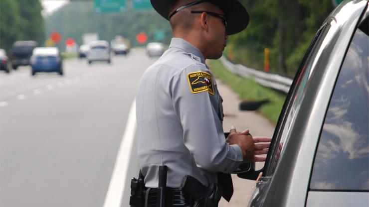Trooper talking to driver pulled over on highway