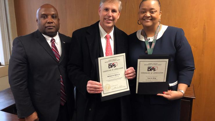 Sec. Hooks posed with two people holding award certificates