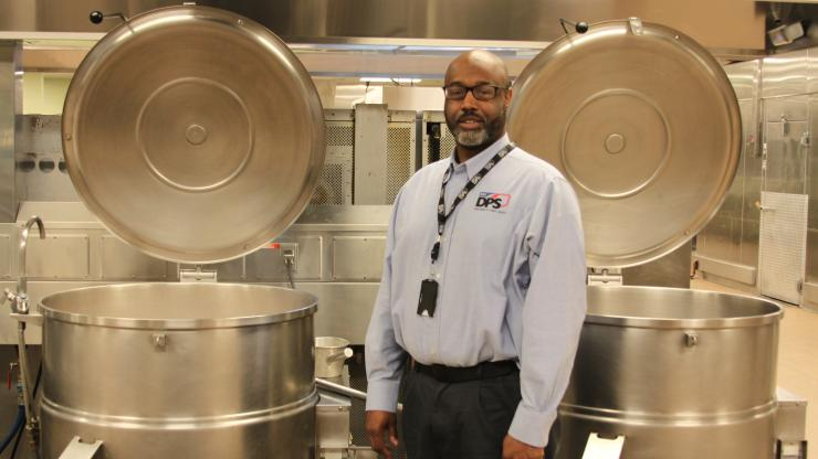 man standing between two large food kettles with open lids