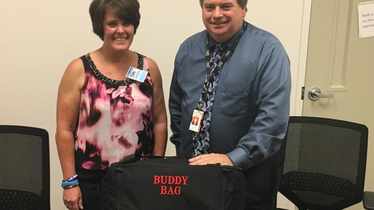 "Man and woman standing behind a black bag with words ""Buddy Bag"" on it in red letters"