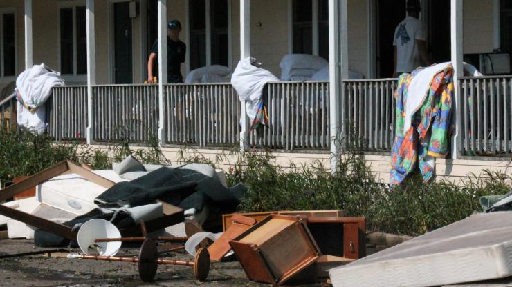 ruined hotel furnishings tossed over porch railing