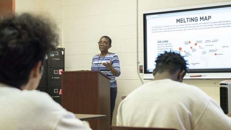 """Woman teaching at a podium. Slide next to her says """"Melting Map,"""" with educational information below."""