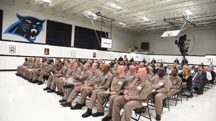 Inmates in brown uniforms sitting in rows in auditorium