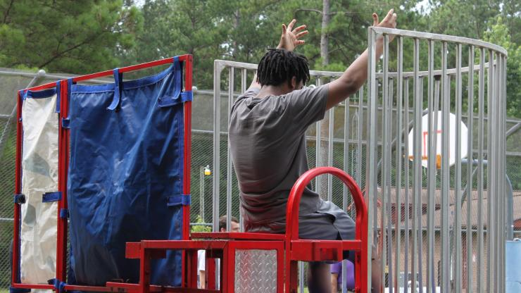 Boy sitting on dunking booth chair with arms raised.