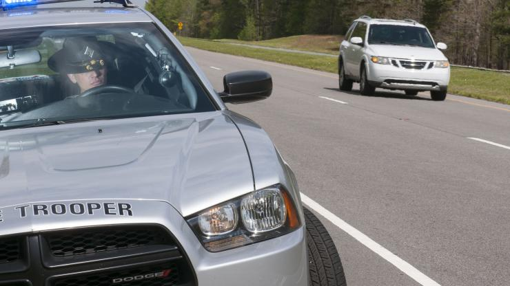 State Highway Patrol Dodge Charger parked on side of highway with Trooper in driver seat