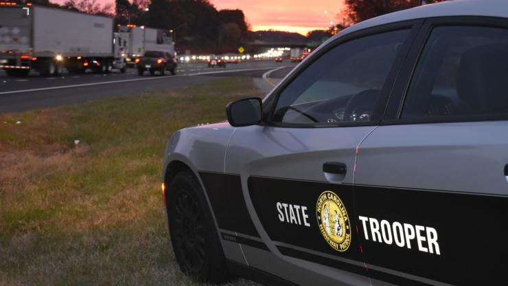 NC Highway Patrol car on side of busy road with sunset in background.