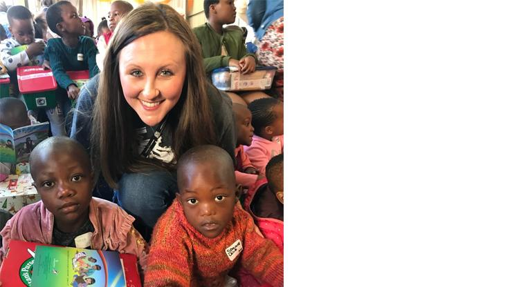 Woman posed with young children holding Operation Christmas Child shoe boxes.