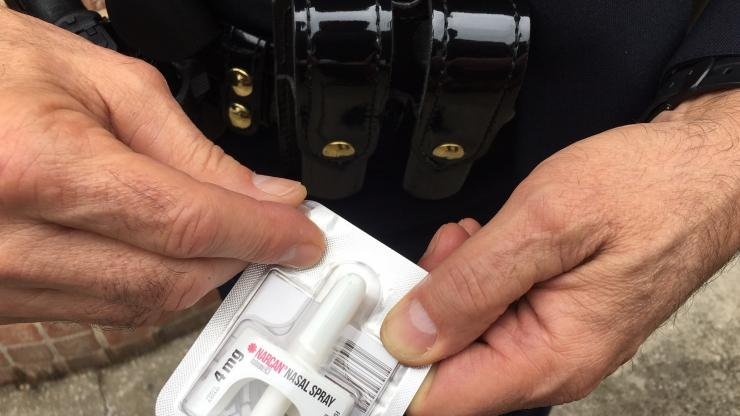 Police officer holding package of Narcan Nasal Spray