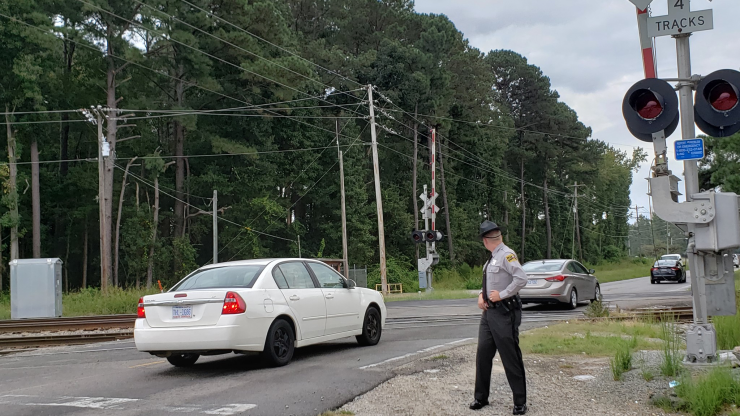 Highway Patrol member standing in front of train tracks with cars passing by