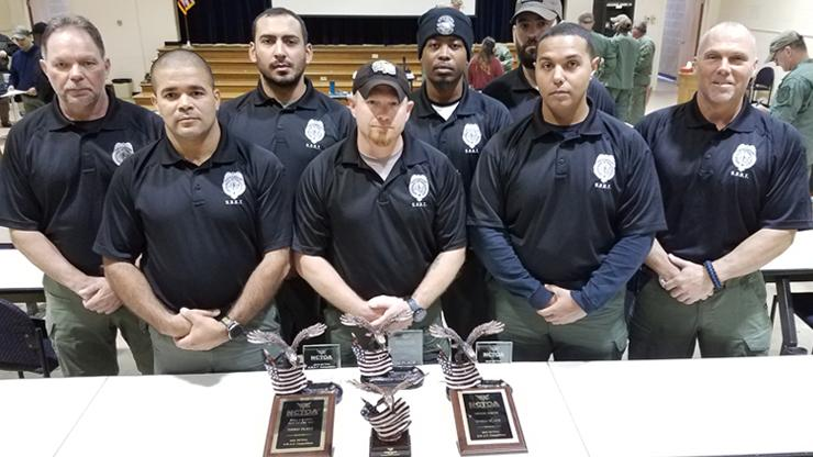 Team of 8 people in black polo shirts and green tactical pants.