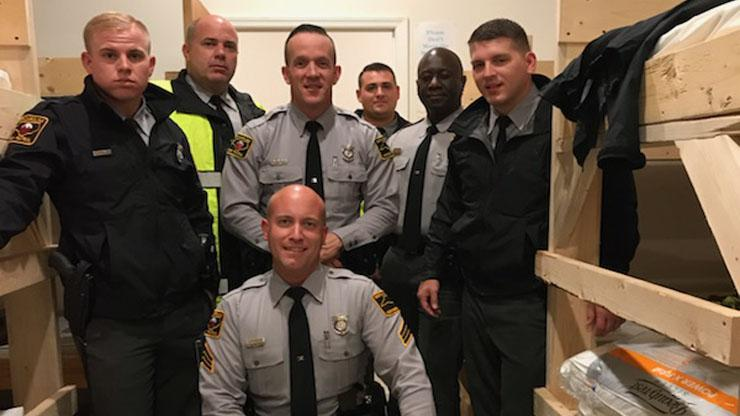 Group of troopers posing around wooden bunk beds