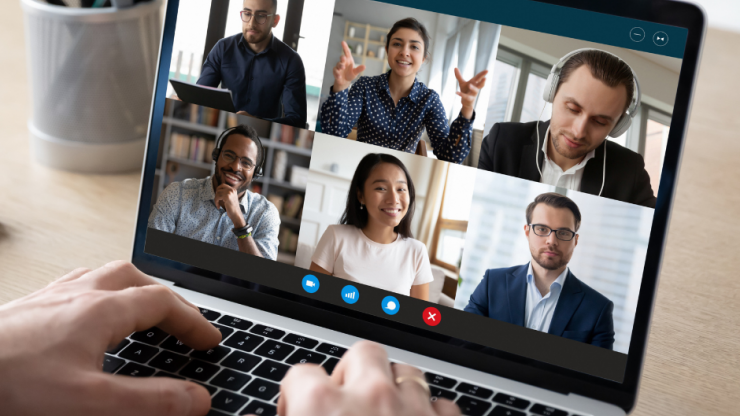 laptop screen with multiple people in a virtual meeting room