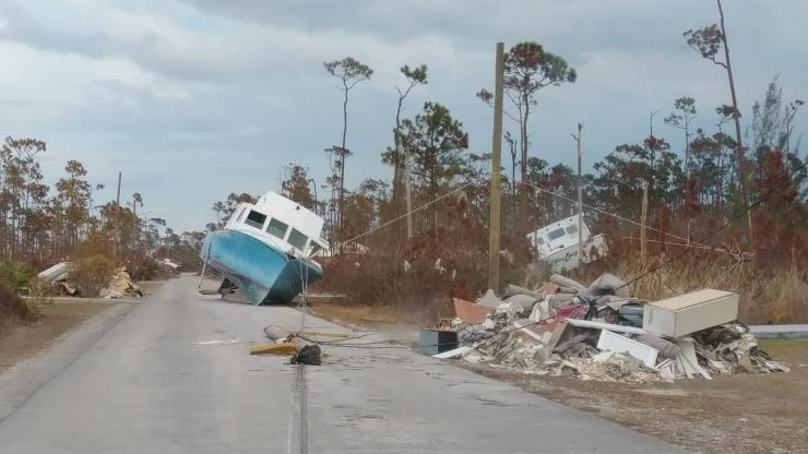 road with boat in middle and debris on side