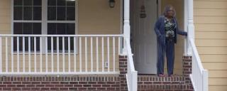 woman standing on front porch of home