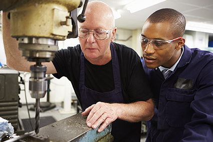 Engineer helps train and apprentice in an industrial setting