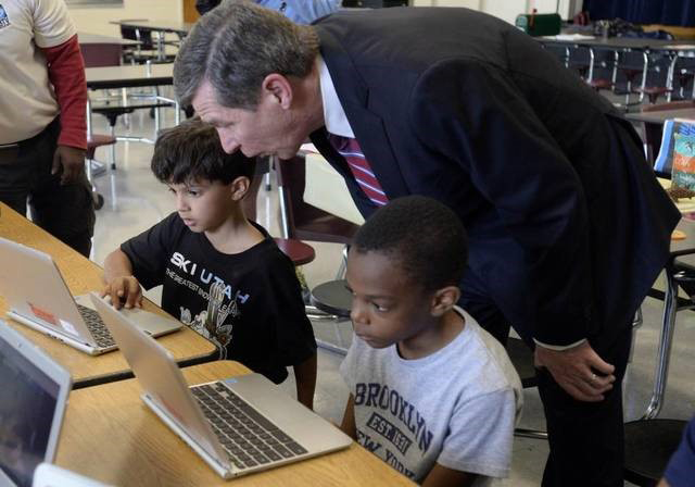 Governor Roy Cooper helps two young boys working with computers