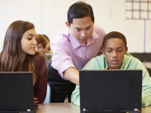 Educator and students at computers