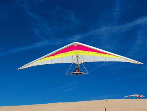Hang glider above sand dunes