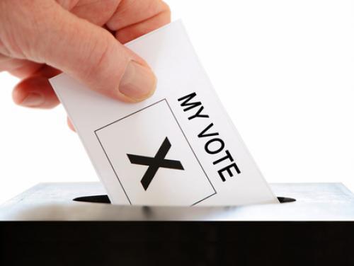 Hand putting a ballot in a ballot box