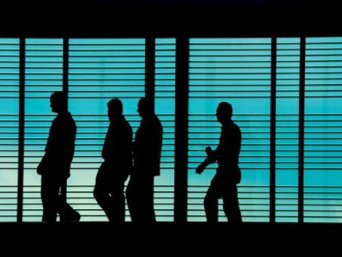 Silhouettes of people walking to work