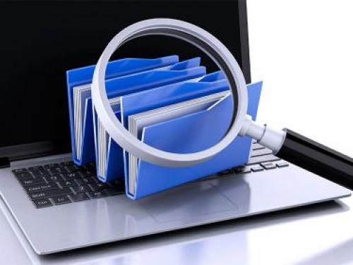 A magnifying glass looking at folders on a laptop