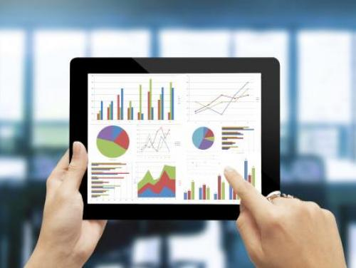 Hands holding a tablet displaying charts and graphs
