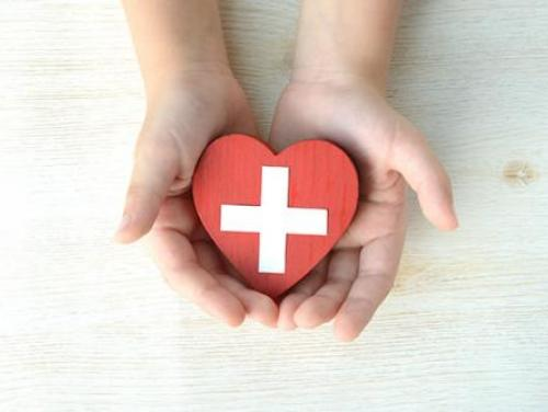 hands holding a red heart with a white cross on it