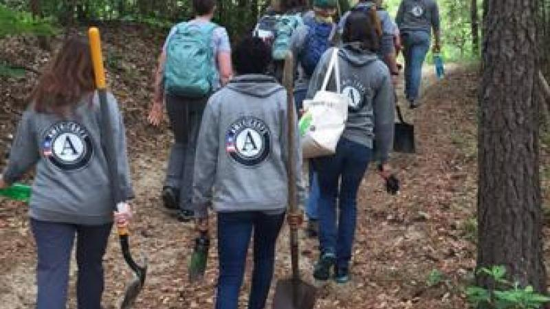 Americorps volunteers hiking through a trail in the forest