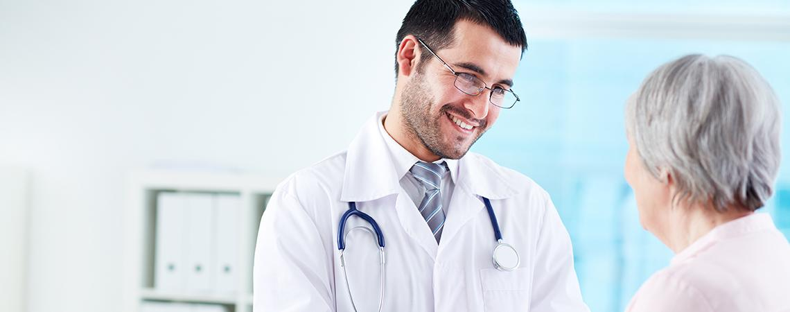 Young male doctor consulting with older female patient