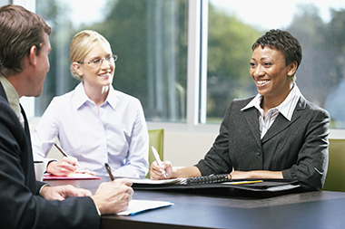 African American business woman in meeting with a young man and woman