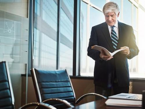 mature lawyer reading paperwork in his office