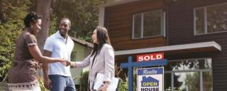 African American couple shake hands with Realtor