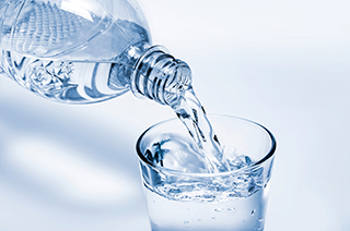 Water being poured into a glass from a bottle
