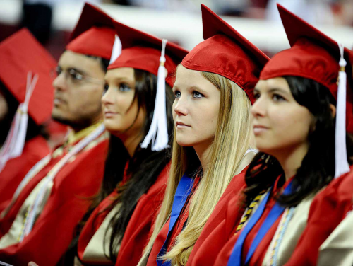 a young man and 3 young women in red graduation caps and gowns
